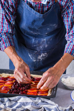 Baking, eating at home, healthy food and lifestyle concept. Senior baker man cooking, kneading fresh dough with hands, rolling with pin, spreading the filling on the pie on a kitchen table with flour 写真素材 - 154506293