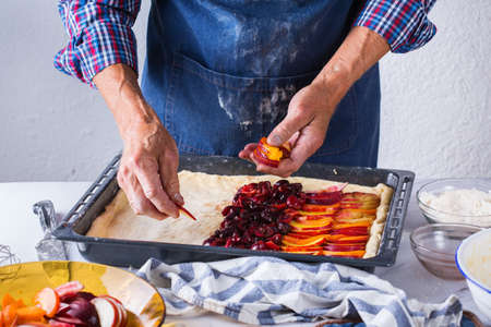 Baking, eating at home, healthy food and lifestyle concept. Senior baker man cooking, kneading fresh dough with hands, rolling with pin, spreading the filling on the pie on a kitchen table with flour 写真素材 - 154506294