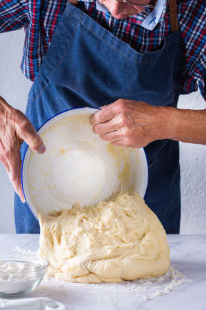 Baking, eating at home, healthy food and lifestyle concept. Senior baker man cooking, kneading fresh dough with hands, rolling with pin, spreading the filling on the pie on a kitchen table with flour 写真素材 - 154506295