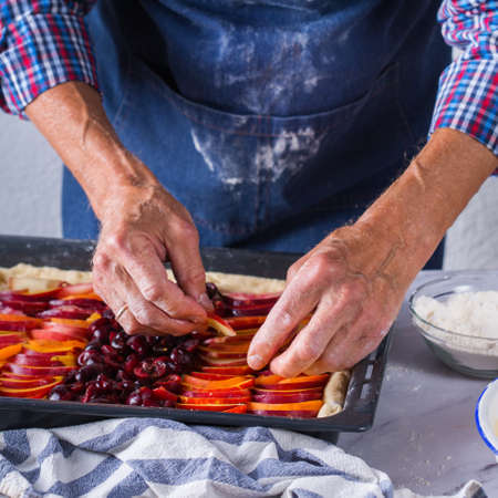 Baking, eating at home, healthy food and lifestyle concept. Senior baker man cooking, kneading fresh dough with hands, rolling with pin, spreading the filling on the pie on a kitchen table with flour 写真素材 - 154506296