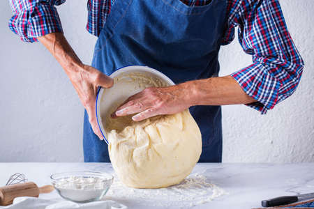Baking, eating at home, healthy food and lifestyle concept. Senior baker man cooking, kneading fresh dough with hands, rolling with pin, spreading the filling on the pie on a kitchen table with flour 写真素材 - 154506297