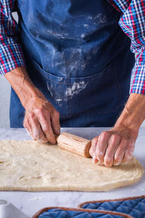 Baking, eating at home, healthy food and lifestyle concept. Senior baker man cooking, kneading fresh dough with hands, rolling with pin, spreading the filling on the pie on a kitchen table with flour 写真素材 - 154506301