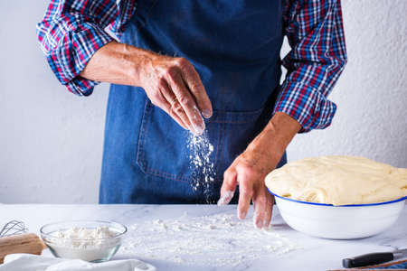 Baking, eating at home, healthy food and lifestyle concept. Senior baker man cooking, kneading fresh dough with hands, rolling with pin, spreading the filling on the pie on a kitchen table with flour 写真素材 - 154506302