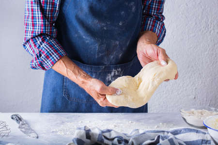 Baking, eating at home, healthy food and lifestyle concept. Senior baker man cooking, kneading fresh dough with hands, rolling with pin, spreading the filling on the pie on a kitchen table with flour 写真素材 - 154506303