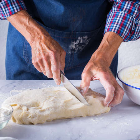 Baking, eating at home, healthy food and lifestyle concept. Senior baker man cooking, kneading fresh dough with hands, rolling with pin, spreading the filling on the pie on a kitchen table with flour 写真素材 - 154506304