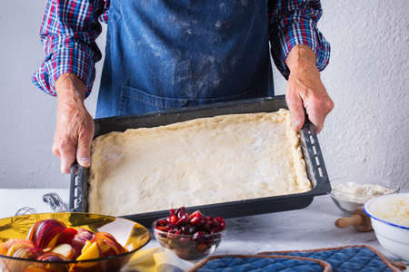 Baking, eating at home, healthy food and lifestyle concept. Senior baker man cooking, kneading fresh dough with hands, rolling with pin, spreading the filling on the pie on a kitchen table with flour 写真素材 - 154506307