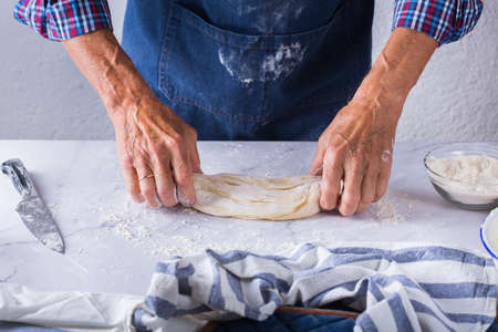 Baking, eating at home, healthy food and lifestyle concept. Senior baker man cooking, kneading fresh dough with hands, rolling with pin, spreading the filling on the pie on a kitchen table with flour 写真素材 - 154506308
