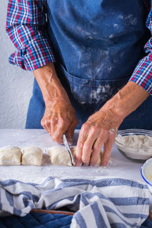 Baking, eating at home, healthy food and lifestyle concept. Senior baker man cooking, kneading fresh dough with hands, rolling with pin, spreading the filling on the pie on a kitchen table with flour 写真素材 - 154506309