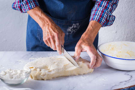 Baking, eating at home, healthy food and lifestyle concept. Senior baker man cooking, kneading fresh dough with hands, rolling with pin, spreading the filling on the pie on a kitchen table with flour 写真素材 - 154506310