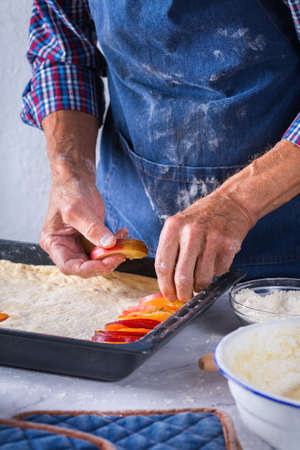Baking, eating at home, healthy food and lifestyle concept. Senior baker man cooking, kneading fresh dough with hands, rolling with pin, spreading the filling on the pie on a kitchen table with flour 写真素材 - 154506312