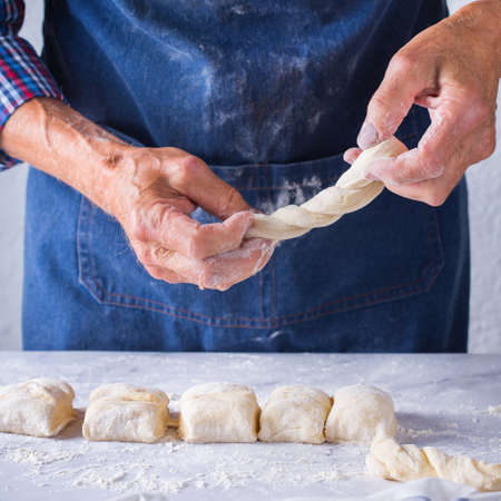 Baking, eating at home, healthy food and lifestyle concept. Senior baker man cooking, kneading fresh dough with hands, rolling with pin, spreading the filling on the pie on a kitchen table with flour 写真素材 - 154506314