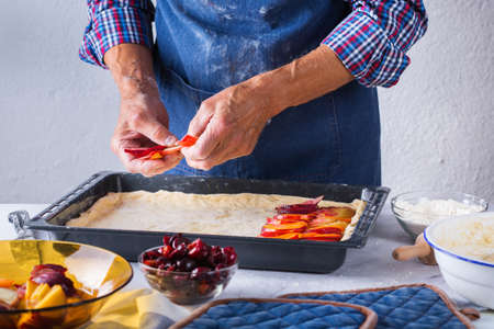 Baking, eating at home, healthy food and lifestyle concept. Senior baker man cooking, kneading fresh dough with hands, rolling with pin, spreading the filling on the pie on a kitchen table with flour 写真素材 - 154506315