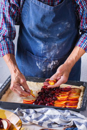 Baking, eating at home, healthy food and lifestyle concept. Senior baker man cooking, kneading fresh dough with hands, rolling with pin, spreading the filling on the pie on a kitchen table with flour 写真素材 - 154506316