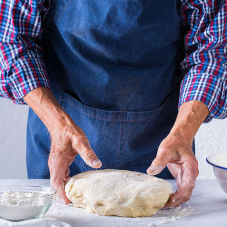 Baking, eating at home, healthy food and lifestyle concept. Senior baker man cooking, kneading fresh dough with hands, rolling with pin, spreading the filling on the pie on a kitchen table with flour 写真素材 - 154506319