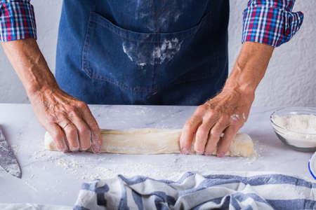 Baking, eating at home, healthy food and lifestyle concept. Senior baker man cooking, kneading fresh dough with hands, rolling with pin, spreading the filling on the pie on a kitchen table with flour 写真素材 - 154506321