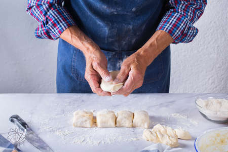 Baking, eating at home, healthy food and lifestyle concept. Senior baker man cooking, kneading fresh dough with hands, rolling with pin, spreading the filling on the pie on a kitchen table with flour 写真素材 - 154506323