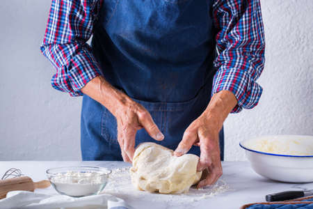 Baking, eating at home, healthy food and lifestyle concept. Senior baker man cooking, kneading fresh dough with hands, rolling with pin, spreading the filling on the pie on a kitchen table with flour 写真素材 - 154506325