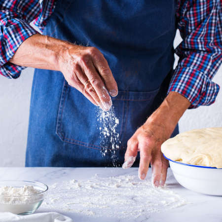 Baking, eating at home, healthy food and lifestyle concept. Senior baker man cooking, kneading fresh dough with hands, rolling with pin, spreading the filling on the pie on a kitchen table with flour 写真素材 - 154506326