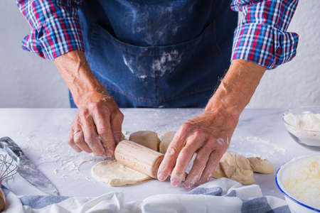 Baking, eating at home, healthy food and lifestyle concept. Senior baker man cooking, kneading fresh dough with hands, rolling with pin, spreading the filling on the pie on a kitchen table with flour 写真素材 - 154506327