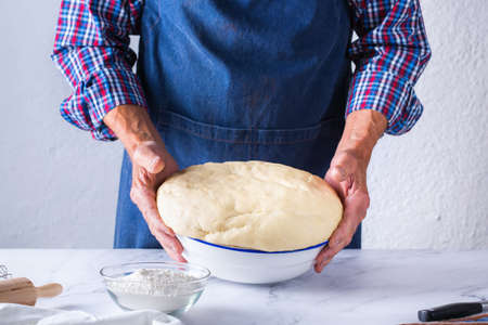 Baking, eating at home, healthy food and lifestyle concept. Senior baker man cooking, kneading fresh dough with hands, rolling with pin, spreading the filling on the pie on a kitchen table with flour 写真素材 - 154506328