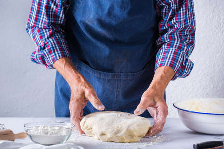 Baking, eating at home, healthy food and lifestyle concept. Senior baker man cooking, kneading fresh dough with hands, rolling with pin, spreading the filling on the pie on a kitchen table with flour 写真素材 - 154506329