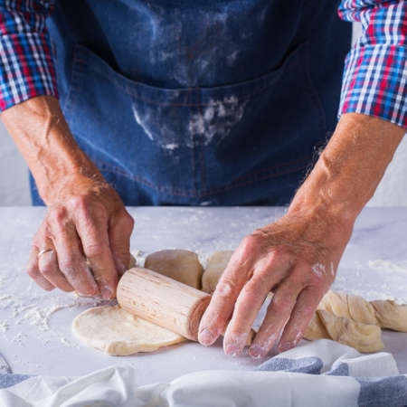 Baking, eating at home, healthy food and lifestyle concept. Senior baker man cooking, kneading fresh dough with hands, rolling with pin, spreading the filling on the pie on a kitchen table with flour 写真素材 - 154506330