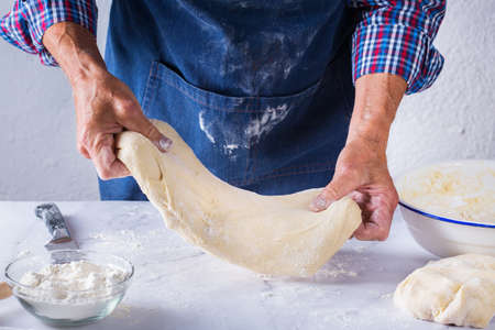 Baking, eating at home, healthy food and lifestyle concept. Senior baker man cooking, kneading fresh dough with hands, rolling with pin, spreading the filling on the pie on a kitchen table with flour 写真素材 - 154506331
