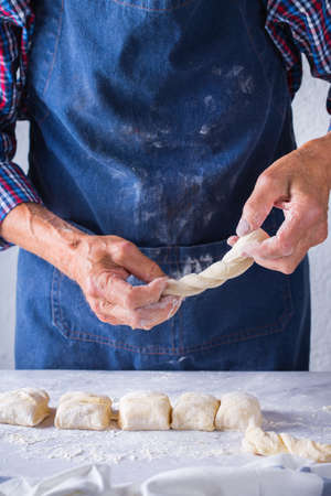 Baking, eating at home, healthy food and lifestyle concept. Senior baker man cooking, kneading fresh dough with hands, rolling with pin, spreading the filling on the pie on a kitchen table with flour 写真素材 - 154506332