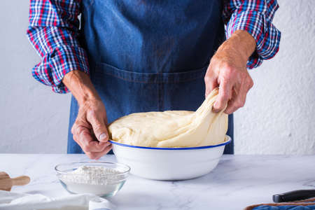 Baking, eating at home, healthy food and lifestyle concept. Senior baker man cooking, kneading fresh dough with hands, rolling with pin, spreading the filling on the pie on a kitchen table with flour 写真素材 - 154506333
