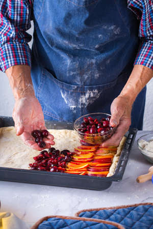 Baking, eating at home, healthy food and lifestyle concept. Senior baker man cooking, kneading fresh dough with hands, rolling with pin, spreading the filling on the pie on a kitchen table with flour 写真素材 - 154506336