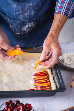 Baking, eating at home, healthy food and lifestyle concept. Senior baker man cooking, kneading fresh dough with hands, rolling with pin, spreading the filling on the pie on a kitchen table with flour 写真素材 - 154506337