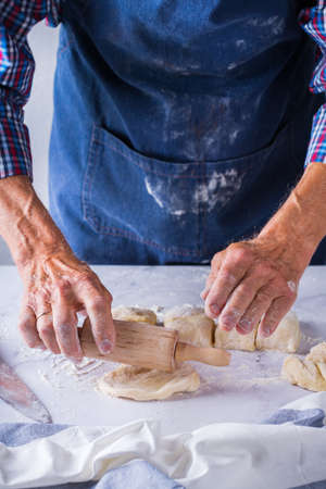 Baking, eating at home, healthy food and lifestyle concept. Senior baker man cooking, kneading fresh dough with hands, rolling with pin, spreading the filling on the pie on a kitchen table with flour 写真素材 - 154506339