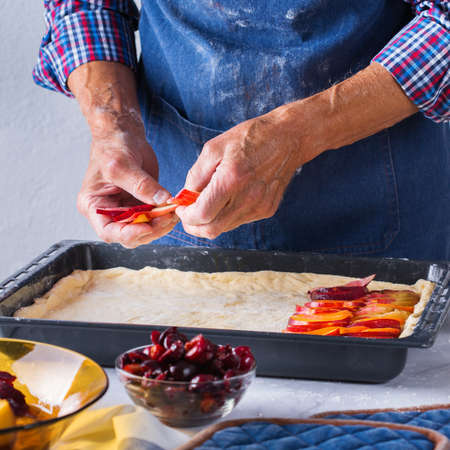 Baking, eating at home, healthy food and lifestyle concept. Senior baker man cooking, kneading fresh dough with hands, rolling with pin, spreading the filling on the pie on a kitchen table with flour 写真素材 - 154506340