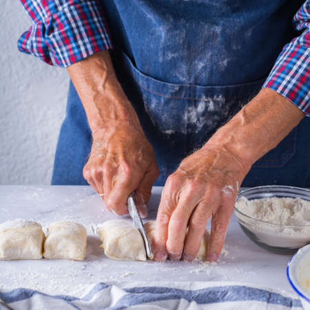 Baking, eating at home, healthy food and lifestyle concept. Senior baker man cooking, kneading fresh dough with hands, rolling with pin, spreading the filling on the pie on a kitchen table with flour 写真素材 - 154506341