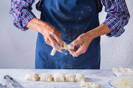 Baking, eating at home, healthy food and lifestyle concept. Senior baker man cooking, kneading fresh dough with hands, rolling with pin, spreading the filling on the pie on a kitchen table with flour 写真素材 - 154506342
