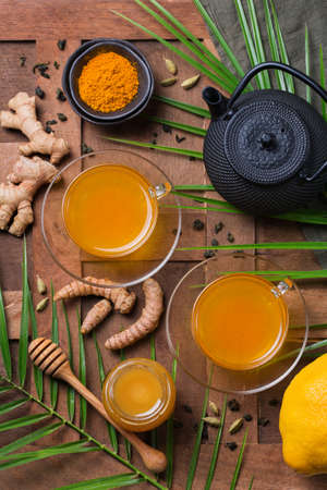 Healthy immune system booster, cold and flu remedy. Turmeric ginger lemon beverage, anti inflammatory smoothie, autumn and winter drink. Detox, clean eating, dieting concept. 写真素材
