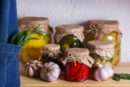 Preserved and fermented food. Assortment of homemade jars with variety of pickled and marinated vegetables on a shelf in the storage room. Housekeeping, home economics, harvest preservation