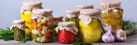 Preserved and fermented food. Assortment of homemade jars with variety of pickled and marinated vegetables on a wooden table. Housekeeping, home economics, harvest preservation. Banner