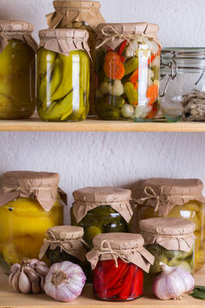 Preserved and fermented food. Assortment of homemade jars with variety of pickled and marinated vegetables on a shelf in the storage room. Housekeeping, home economics, harvest preservation 写真素材 - 154897389