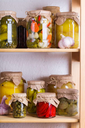 Preserved and fermented food. Assortment of homemade jars with variety of pickled and marinated vegetables on a shelf in the storage room. Housekeeping, home economics, harvest preservation 写真素材 - 154897558