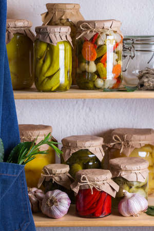 Preserved and fermented food. Assortment of homemade jars with variety of pickled and marinated vegetables on a shelf in the storage room. Housekeeping, home economics, harvest preservation 写真素材 - 154897301