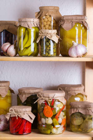 Preserved and fermented food. Assortment of homemade jars with variety of pickled and marinated vegetables on a shelf in the storage room. Housekeeping, home economics, harvest preservation 写真素材 - 154897080