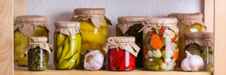 Preserved and fermented food. Assortment of homemade jars with variety of pickled and marinated vegetables on a shelf in the storage room. Housekeeping, home economics, harvest preservation. Banner