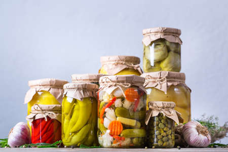 Preserved and fermented food. Assortment of homemade jars with variety of pickled and marinated vegetables on a wooden table. Housekeeping, home economics, harvest preservation 写真素材