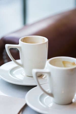 Two empty coffee cups on a table in a cafe. Lifestyle composition with natural light 写真素材