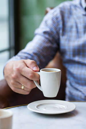 Young successful businessman sitting in a cafe and drinking morning coffee. Lifestyle composition with natural light 写真素材