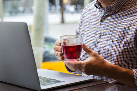 Young successful businessman sitting in a cafe, drinking healthy red tea and working on a laptop. Lifestyle composition with natural light
