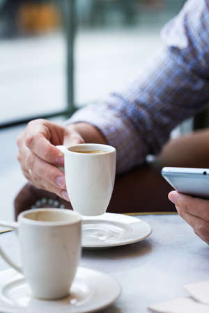 Young successful businessman sitting in a cafe, drinking morning coffee and using smartphone. Lifestyle composition with natural light