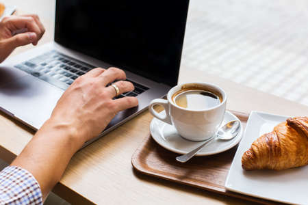 Young man, freelancer sitting in a cafe, drinking coffee and working on a laptop. Lifestyle composition with natural light