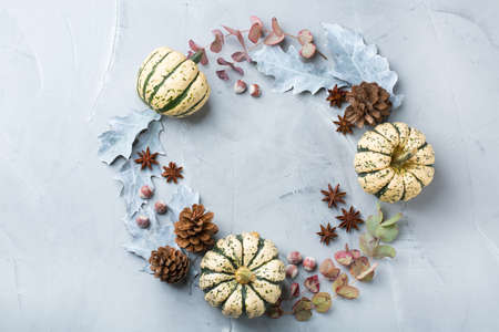 Creative Christmas winter autumn fall day composition with decorative dried leaves and white pumpkins. Flat lay, top view, copy space, still life blue pastel background for greeting card